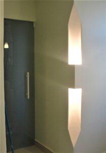 Detalhe da coluna de iluminação indireta na passagem para o hall de circulação.