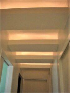 Detalhe do teto flutuante com iluminação indireta.